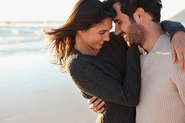 smiling couple hugging on beach - couples romance stock pictures, royalty-free photos & images