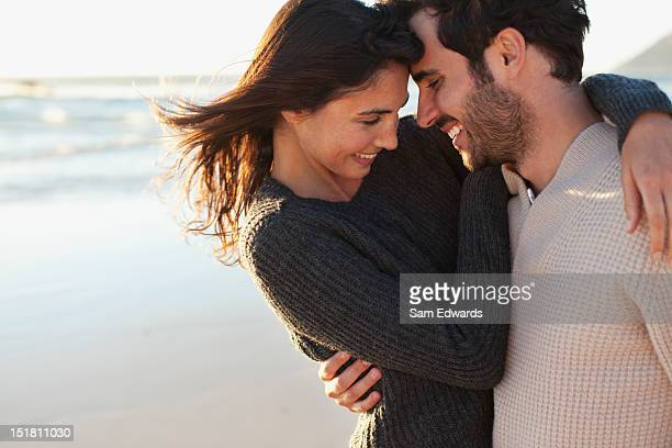 smiling couple hugging on beach - verlieben stock-fotos und bilder