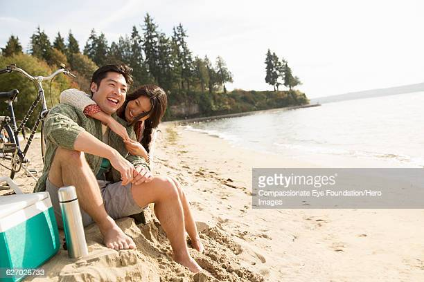 smiling couple hugging on beach - photography stock pictures, royalty-free photos & images