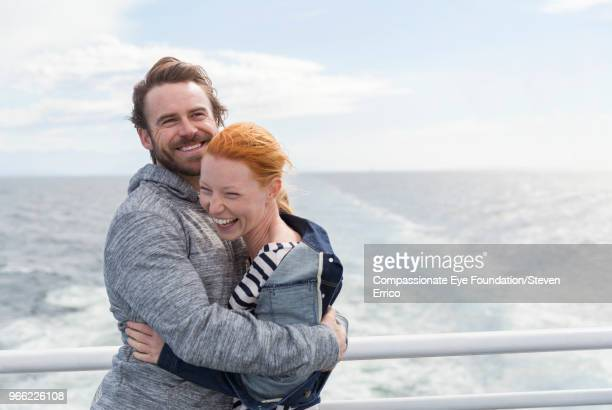 Smiling couple hugging on boat deck
