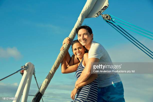 Smiling couple hugging on sailboat