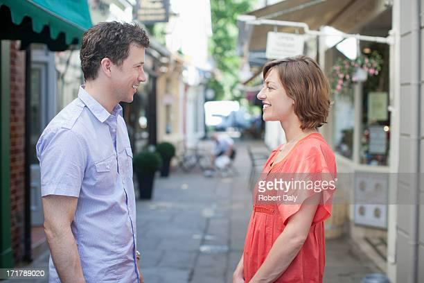Sonriente pareja abrazándose al aire libre en la ciudad