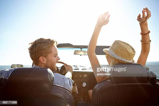 Smiling couple in a convertible on a sunny day