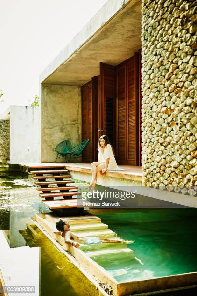 Smiling couple in discussion while relaxing by plunge pool outside of bungalow at luxury tropical resort