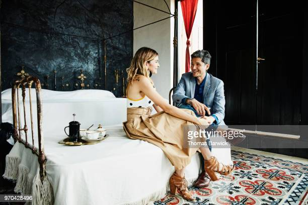 Smiling couple in discussion while sitting on bed in boutique hotel before going out