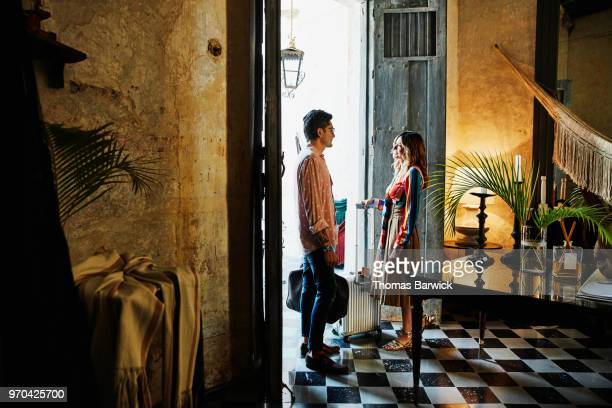 Smiling couple in discussion while standing in lobby of boutique hotel