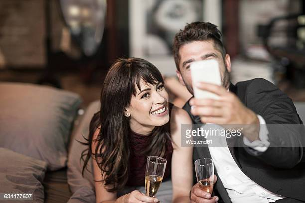 smiling couple in elegant clothing drinking champagne in bed and taking a selfie - mid adult couple stock pictures, royalty-free photos & images