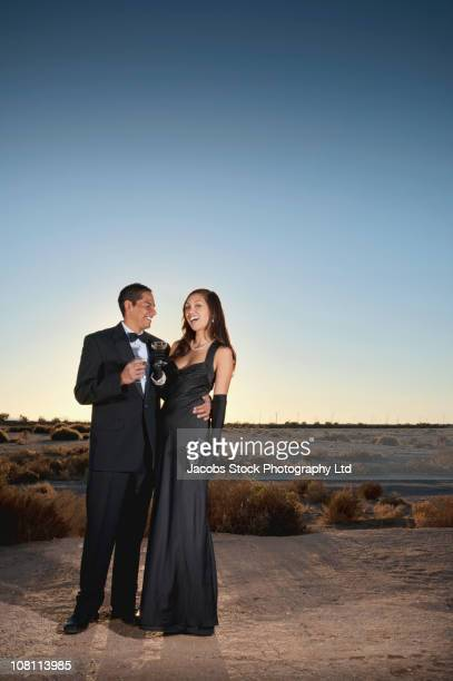 Smiling couple in formal attire drinking champagne in desert