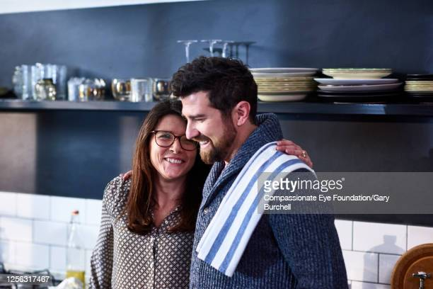 smiling couple in kitchen - wife stock pictures, royalty-free photos & images