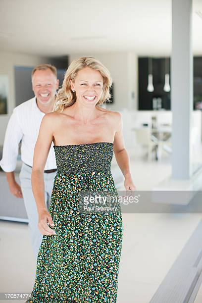 smiling couple in living room - strapless dress stock pictures, royalty-free photos & images
