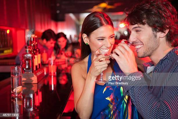 Sonriente pareja en un club nocturno con bebidas