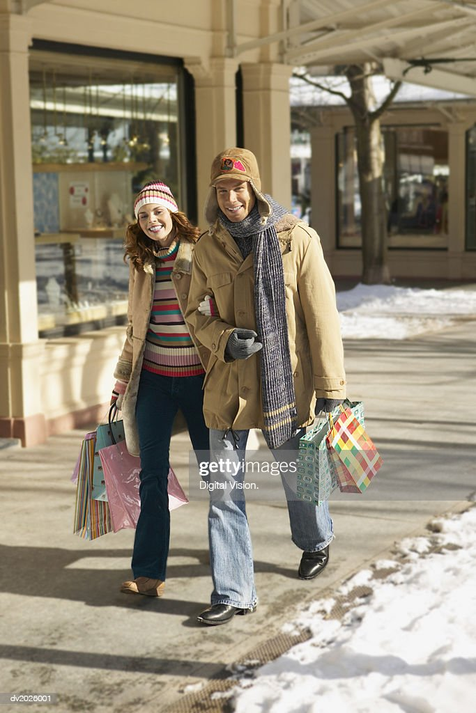 Smiling Couple in Winter Outfits Walk Arm in Arm on the Pavement Carrying Shopping Bags : Stock Photo