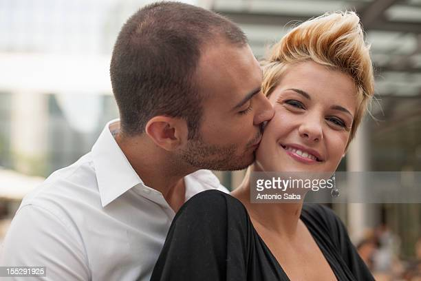 Smiling couple kissing outdoors