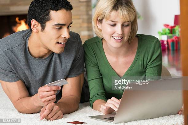 smiling couple laying on carpet shopping online with laptop - fund fair stock photos and pictures