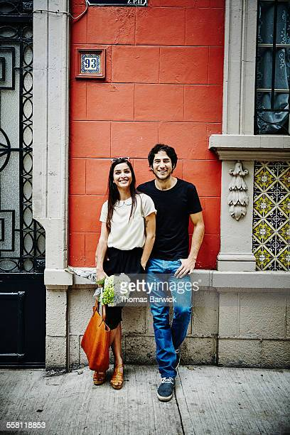 Smiling couple leaning against building