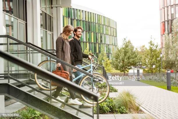 Smiling couple leaving house with bicycles