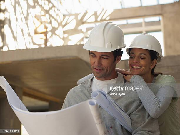 Smiling couple looking at blueprints