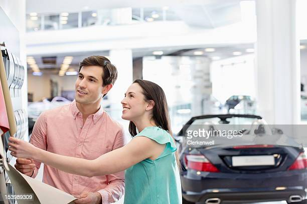 Smiling couple looking at color swatches in car dealership showroom