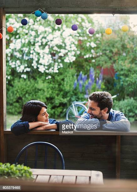 Smiling couple looking at each while leaning on log cabin
