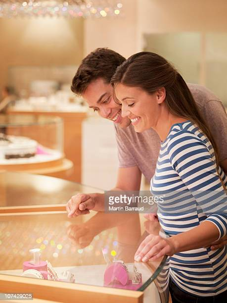 smiling couple looking at jewelry case - jewelry store stock pictures, royalty-free photos & images