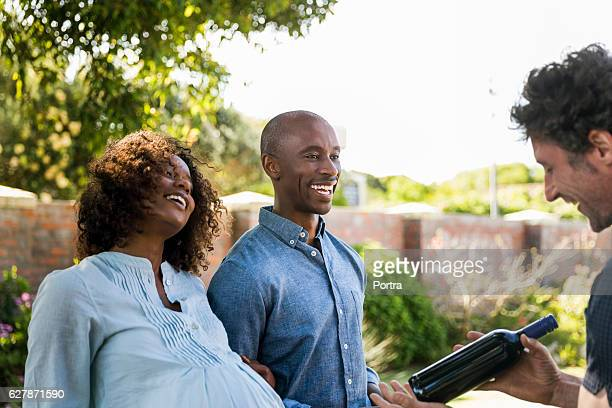 Smiling couple looking at man holding wine bottle
