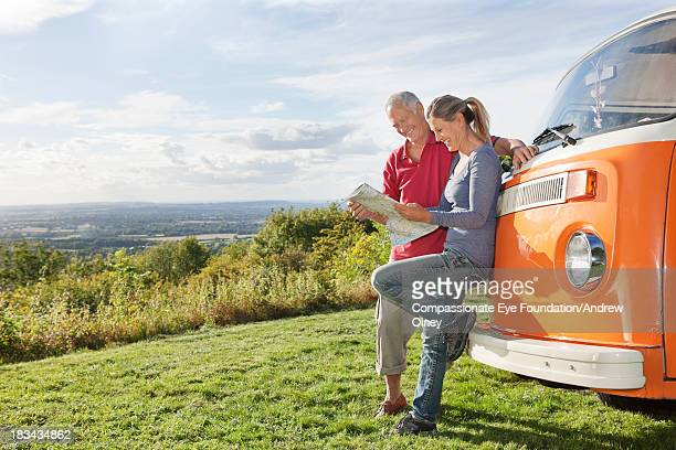 Smiling couple looking at map by camper van