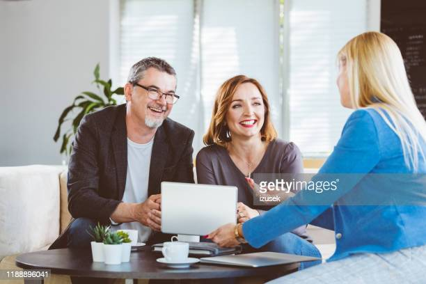 smiling couple looking at psychotherapist - manager stock pictures, royalty-free photos & images