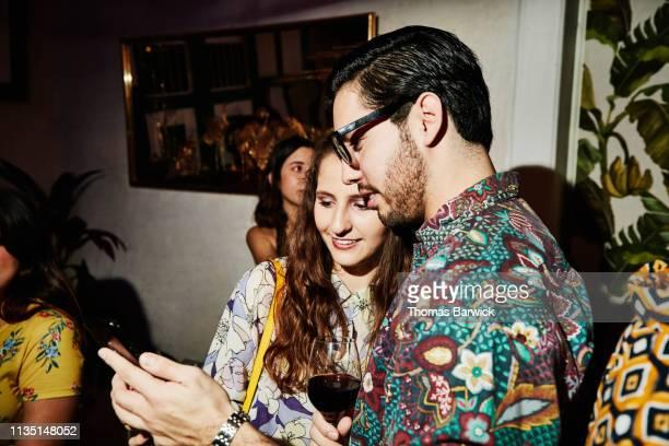 smiling couple looking at smart phone during party in night club - atividade romântica - fotografias e filmes do acervo