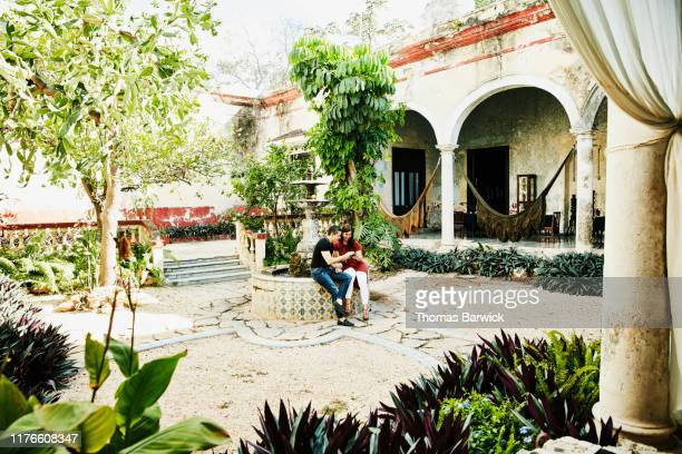 Smiling couple looking at smart phone while touring courtyard of villa