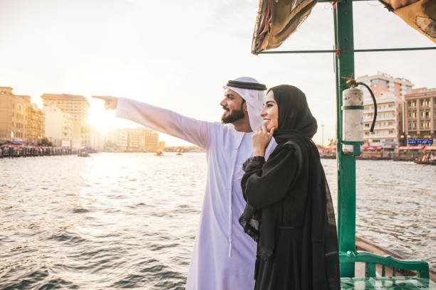 Smiling Couple Looking At View While Standing In Boat On River During Sunset