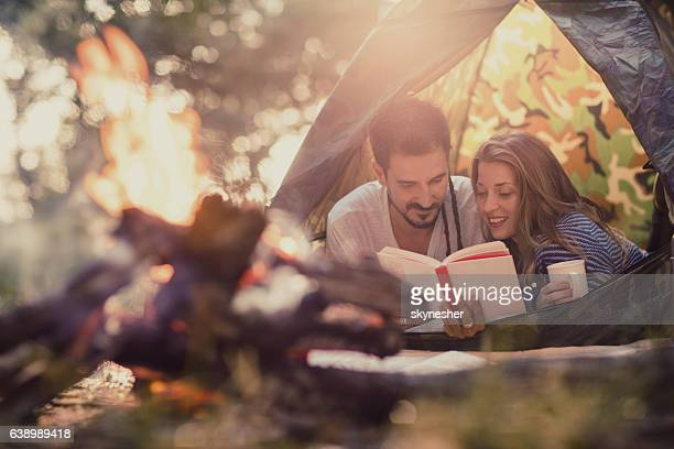 Smiling couple lying in tent and reading a book.