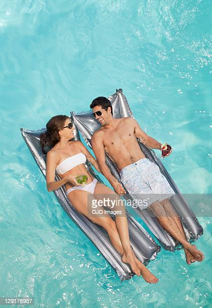 Smiling couple lying on raft while holding glass