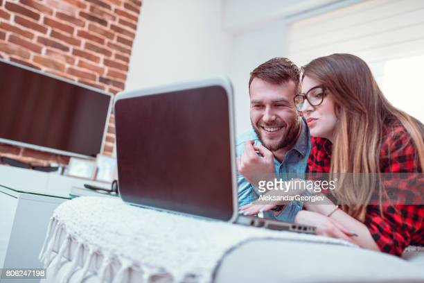 smiling couple lying on sofa and using laptop at home - aleksandar georgiev stock photos and pictures