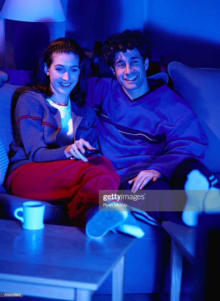 Smiling Couple on a Couch Watching Television : Stock Photo