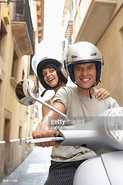 Smiling couple on scooter