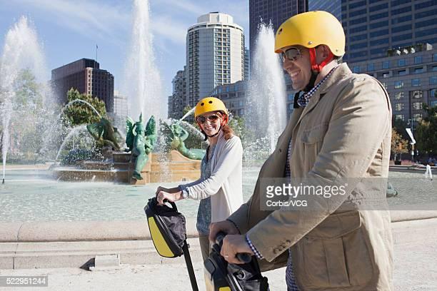 Smiling couple on segway with fountain on background, Philadelphia, Pennsylvania, USA