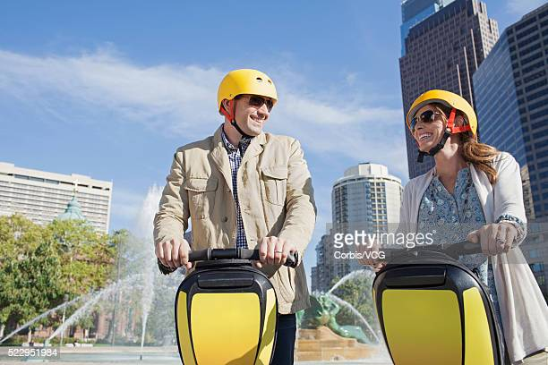 Smiling couple on segway with fountain on background, Philadelphia, Pennsylvania, USA