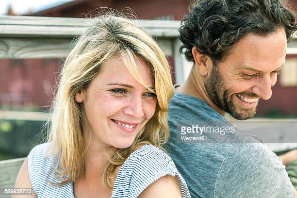 Smiling couple outdoors back to back