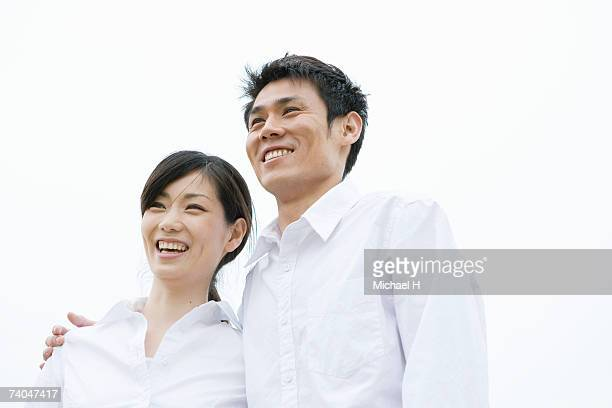 Smiling couple outdoors, low angle view