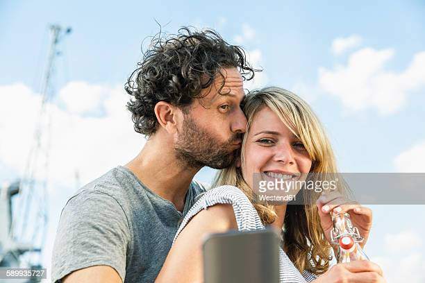 Smiling couple outdoors taking a selfie