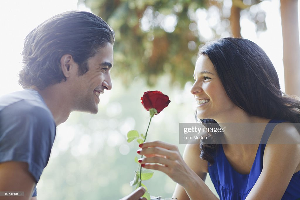 Smiling couple outdoors with red rose : Stock Photo