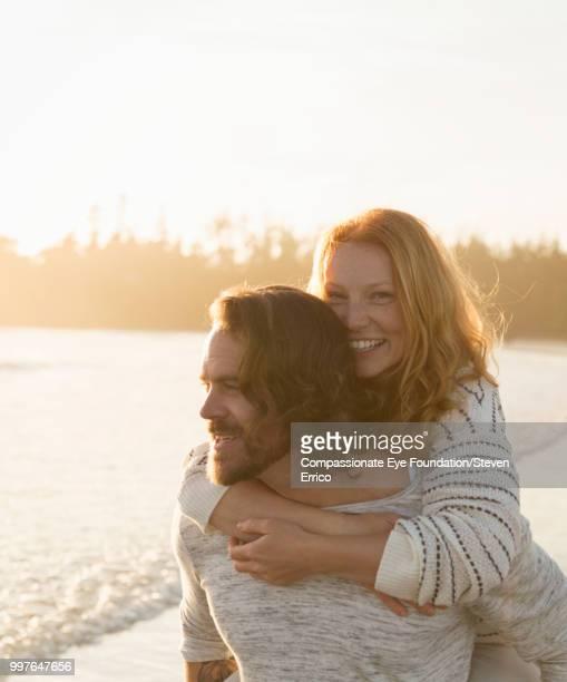 Smiling couple piggybacking on beach at sunset