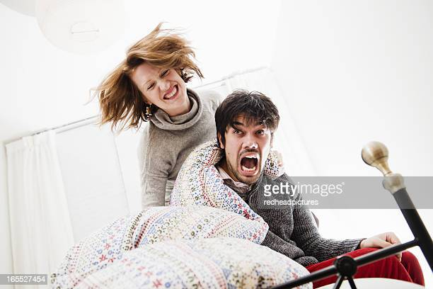smiling couple playing in bed - teasing stock pictures, royalty-free photos & images