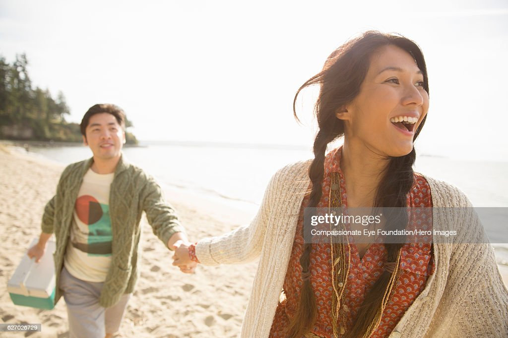 Smiling couple playing on beach : Stock-Foto