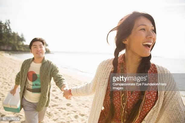 Smiling couple playing on beach