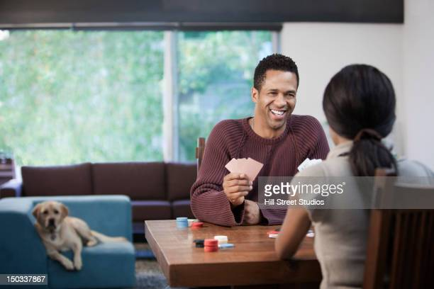 Smiling couple playing poker together