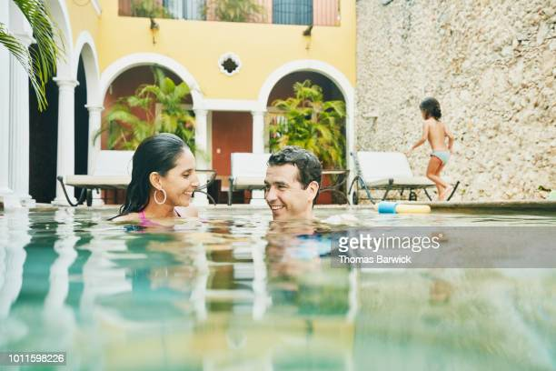 smiling couple playing with family in pool at tropical resort - tourist resort stock pictures, royalty-free photos & images