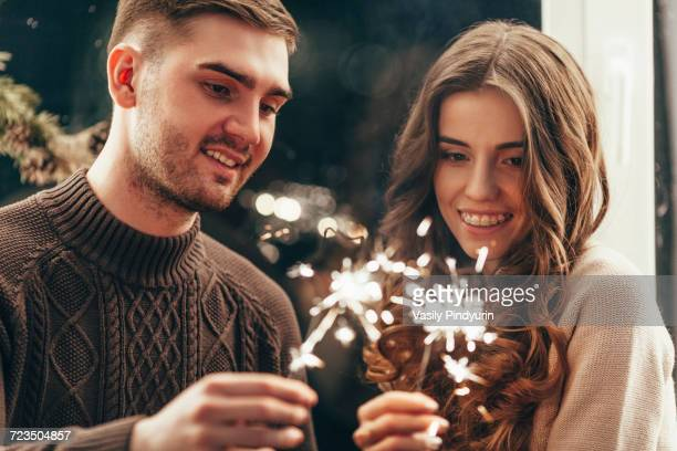 Smiling couple playing with sparklers during Christmas celebration