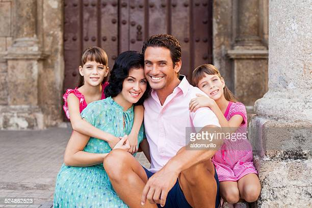 Smiling couple poses with there daughters