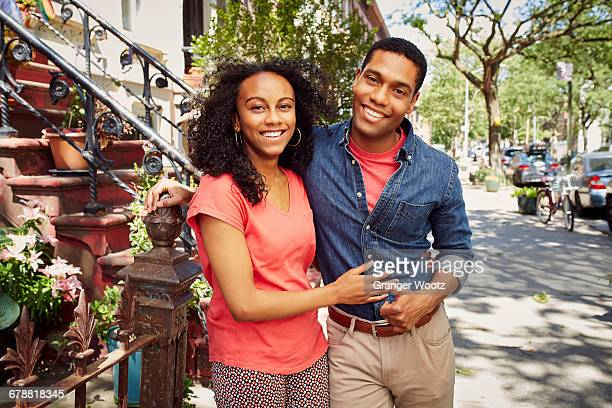 Smiling couple posing on city sidewalk